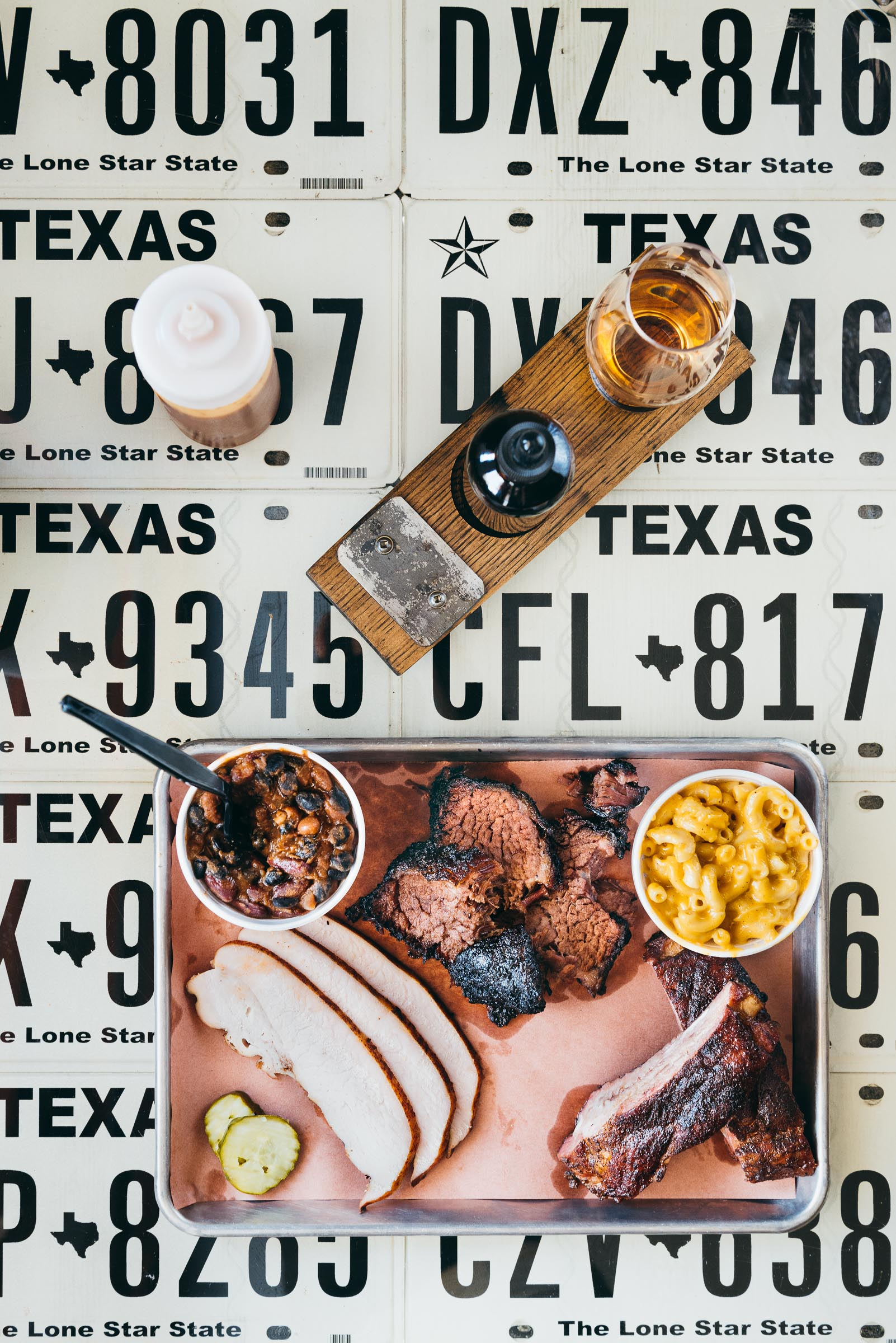 Barbecue, plated on a table made up of Texas license plates. All-The-Kings-Men-Bryan-Texas