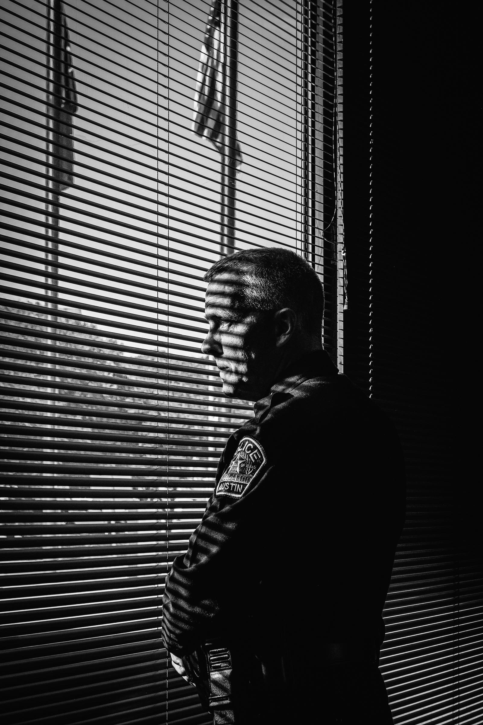 Black-and-white portrait of pensive Austin-Police-Chief-Brian-Manley- peering through blinds.