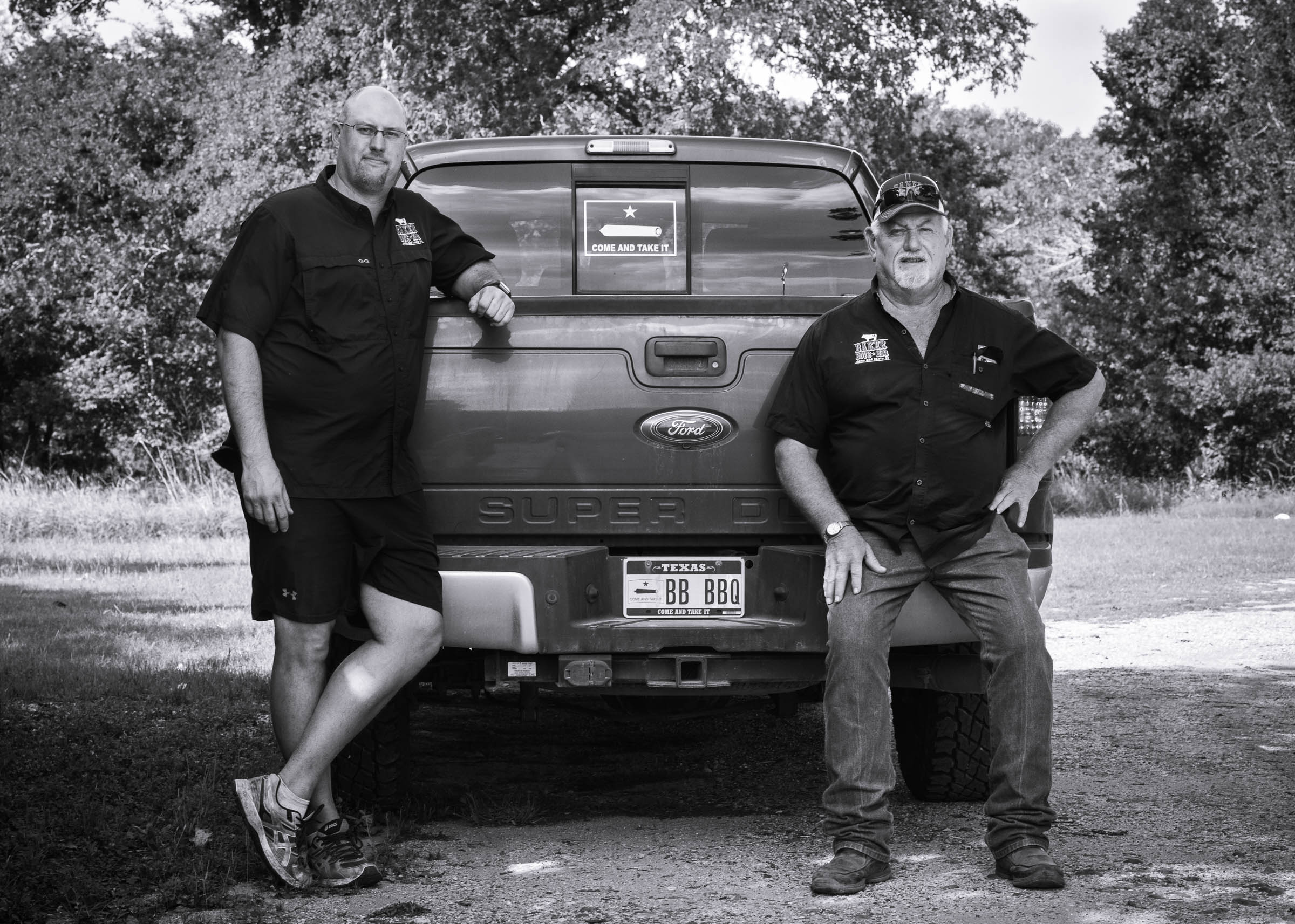 Black-and-white portrait of the owners of Baker-Boys-BBQ, seated on their pick-up truck.