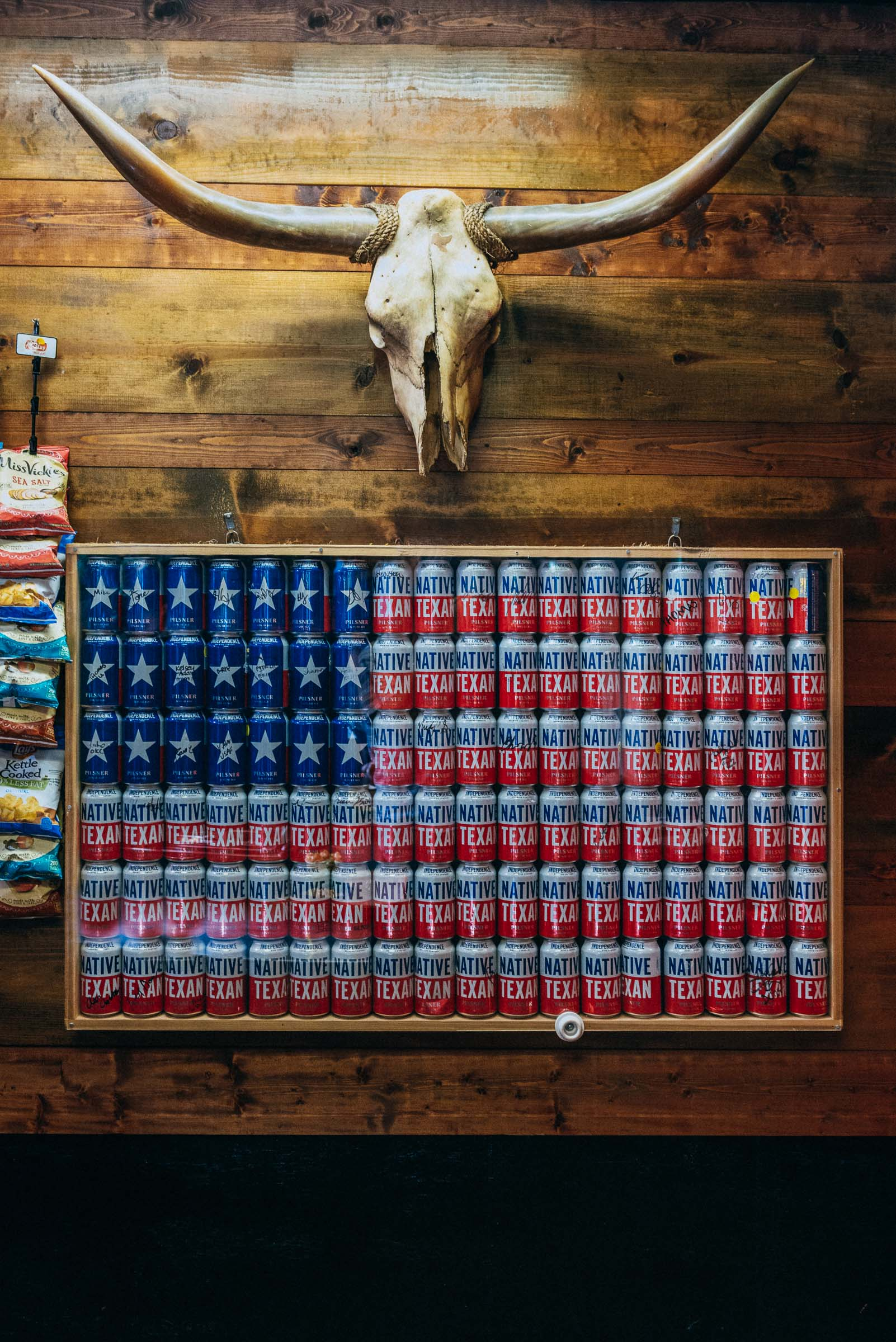 Beer cans arranged in a frame  to make a US flag  beneath a Longhorn skull -Austin-TX