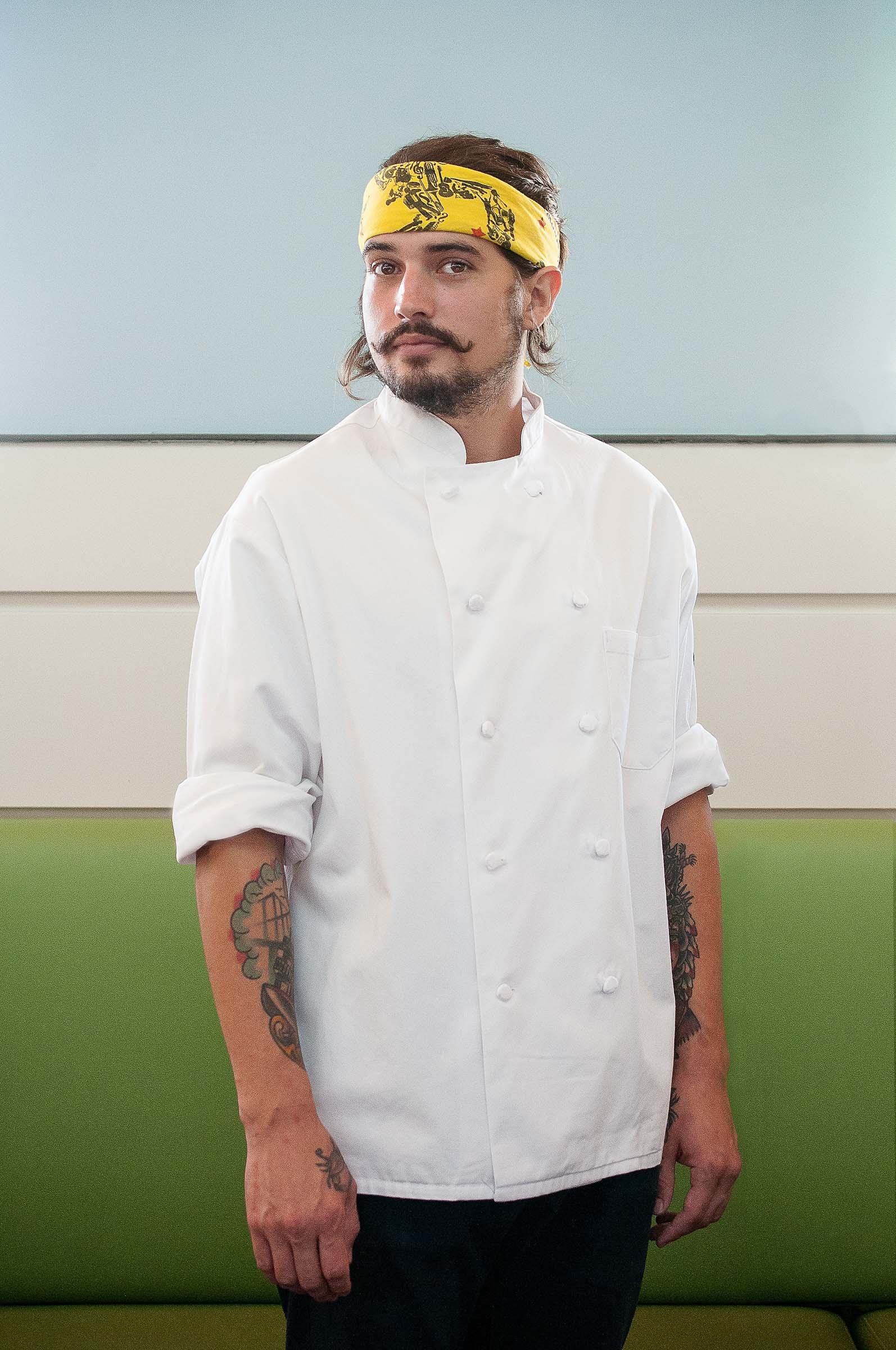 Chef Mark Ball photographed in natural light against green blue backdrop.