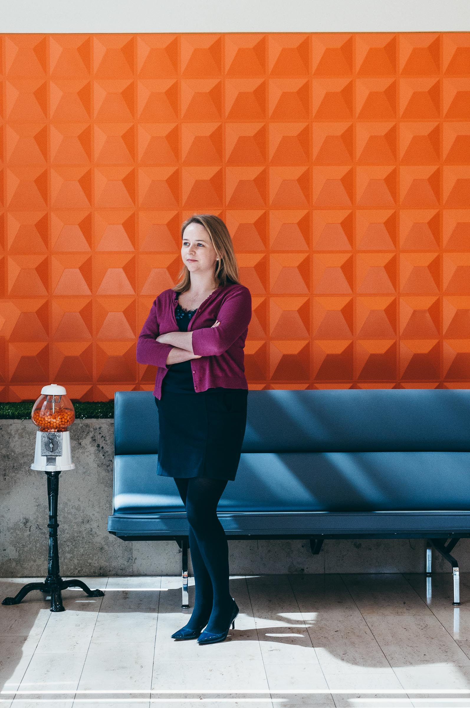 Executive Portrait-Woman standing before orange backdrop at Indeed Austin TX