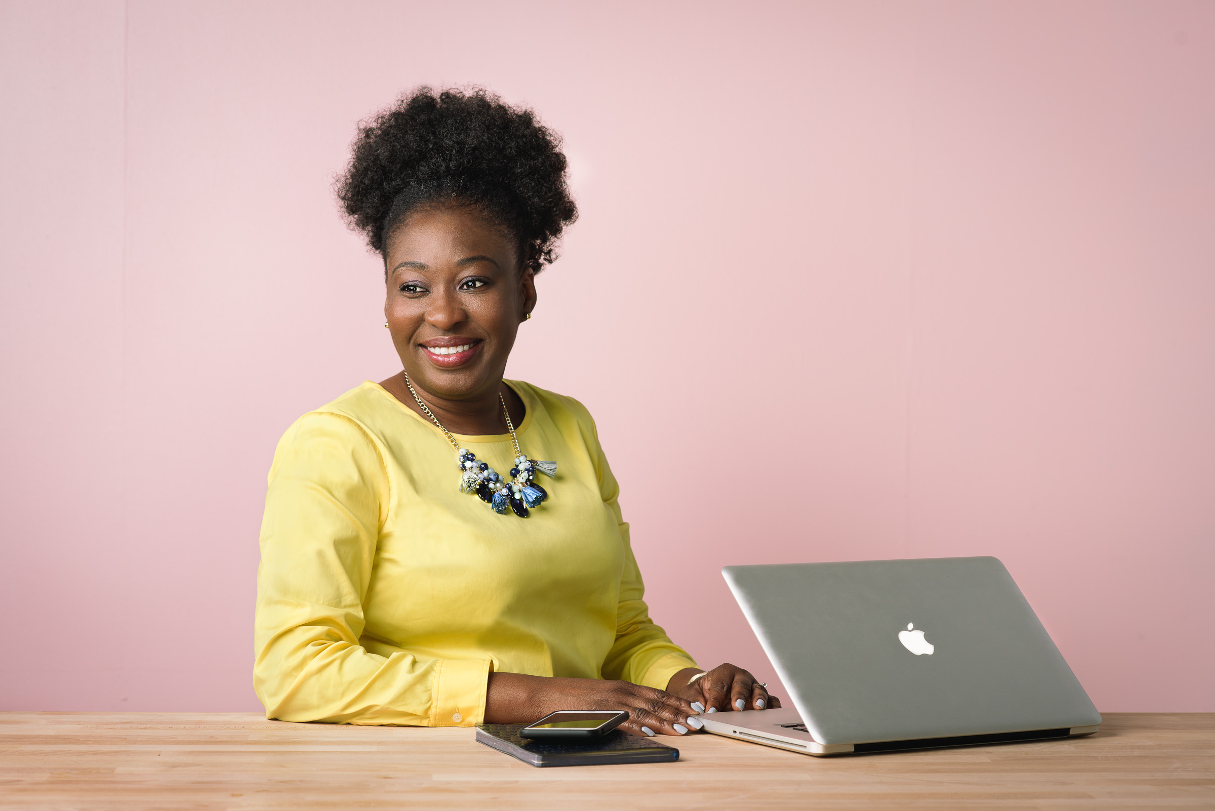 Corporate diversity portrait - Ezinne Udezue in yellow shirt against a pink backdrop.