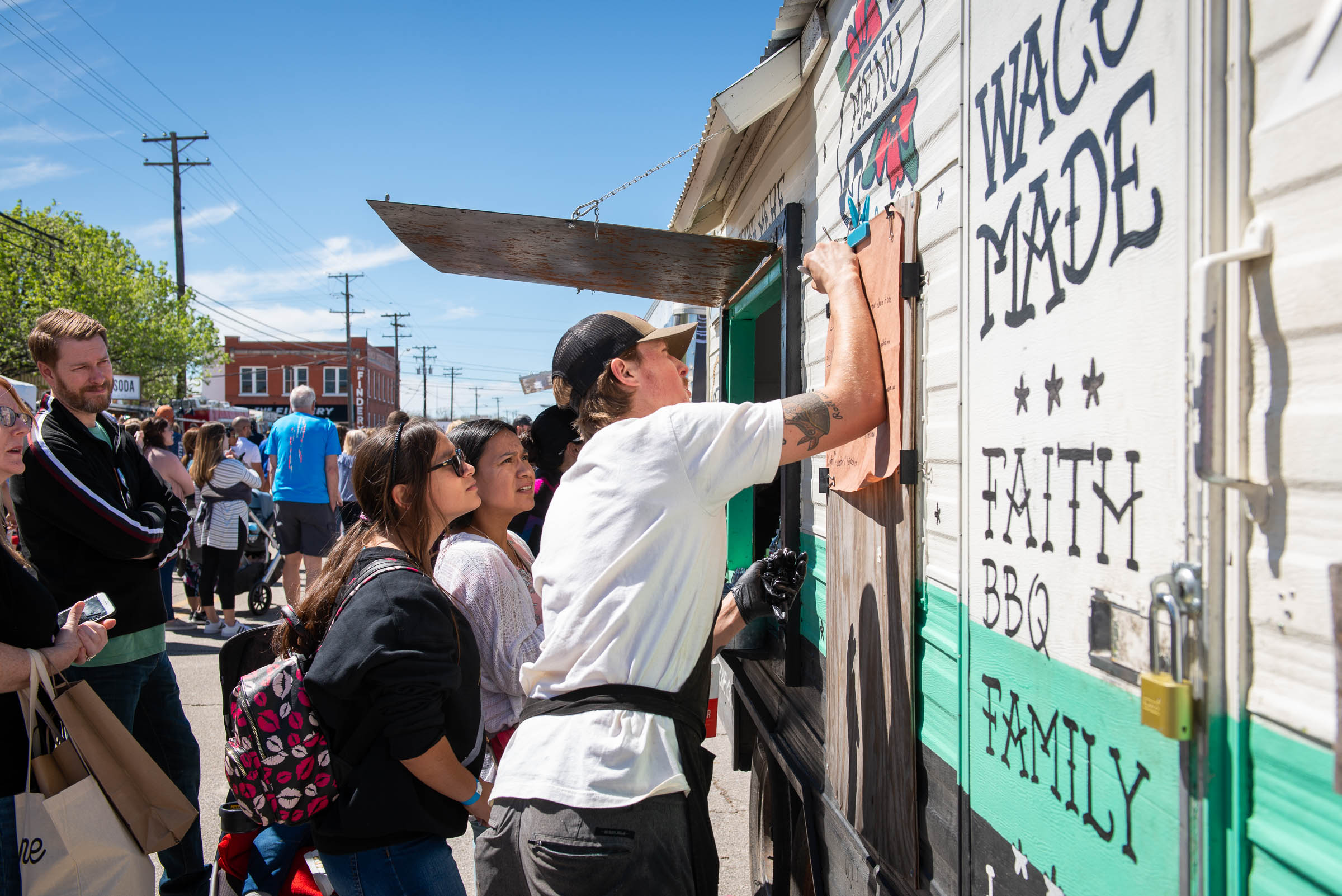 Phillip Helberg updating the hand-written menu on his food truck. Helberg-BBQ-Waco-Texas