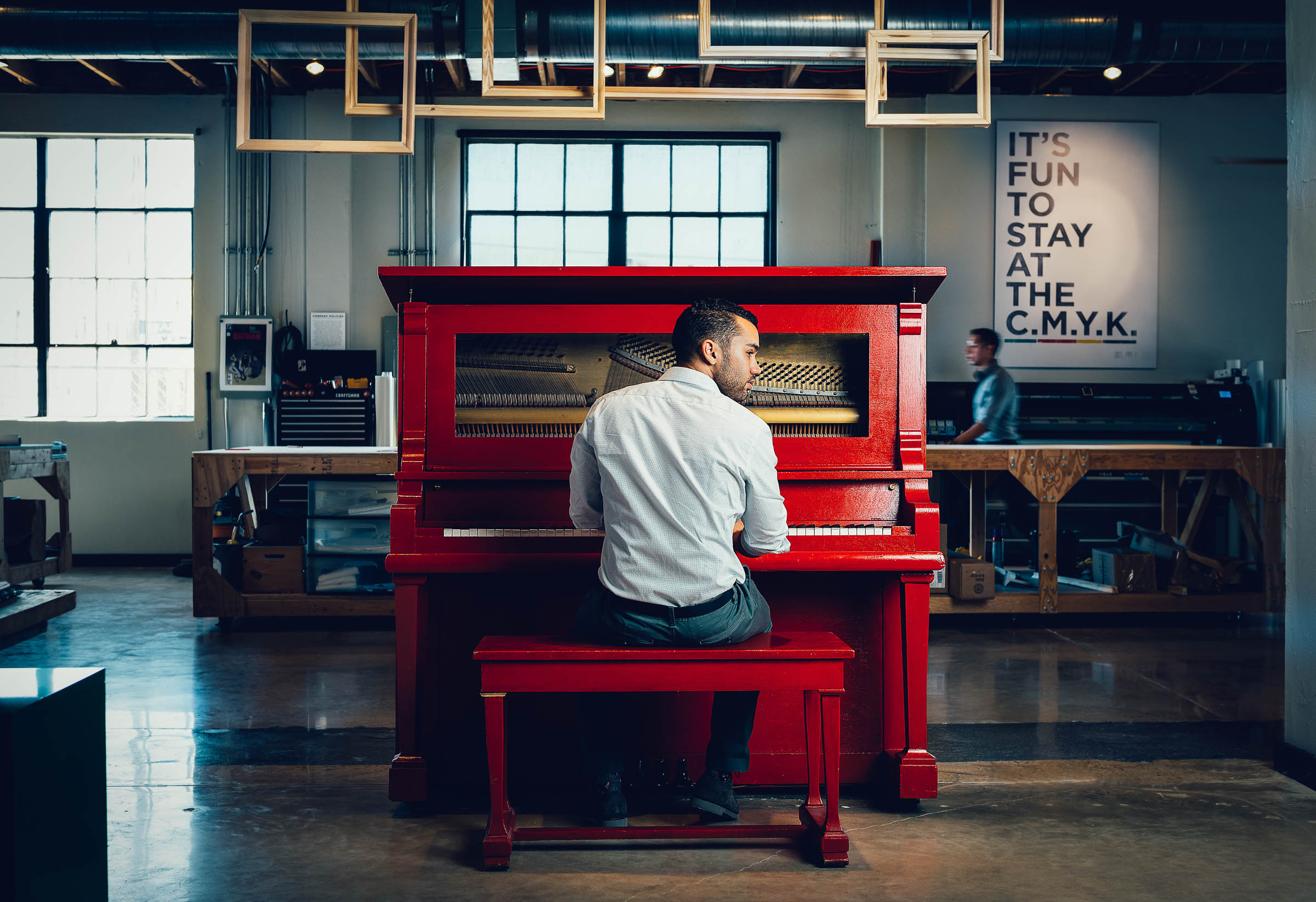 Professional business lifestyle image - Alex Hilmy plays a bright red piano in the centre of his office.
