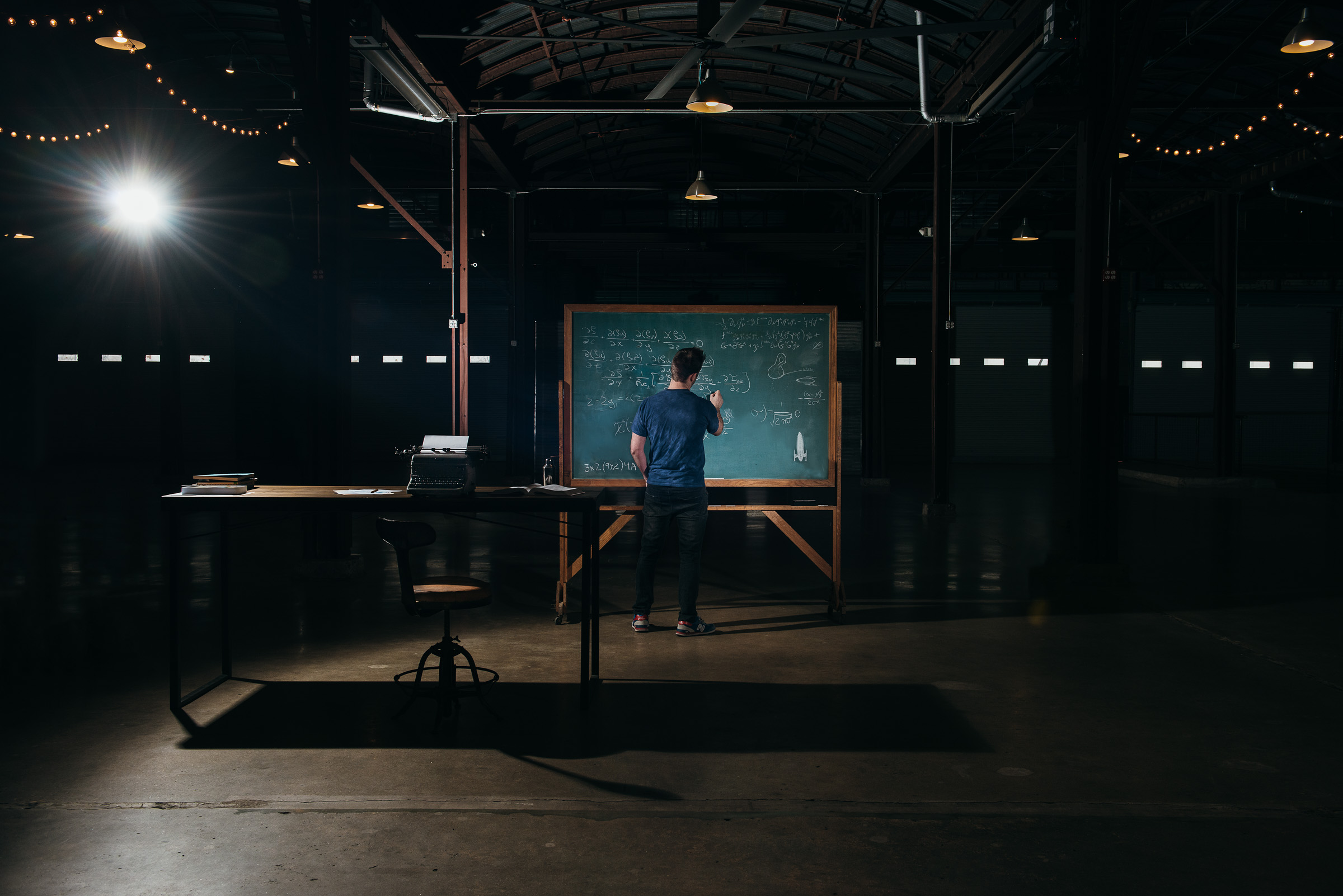 A lone corporate figure working on a chalk board late at night.