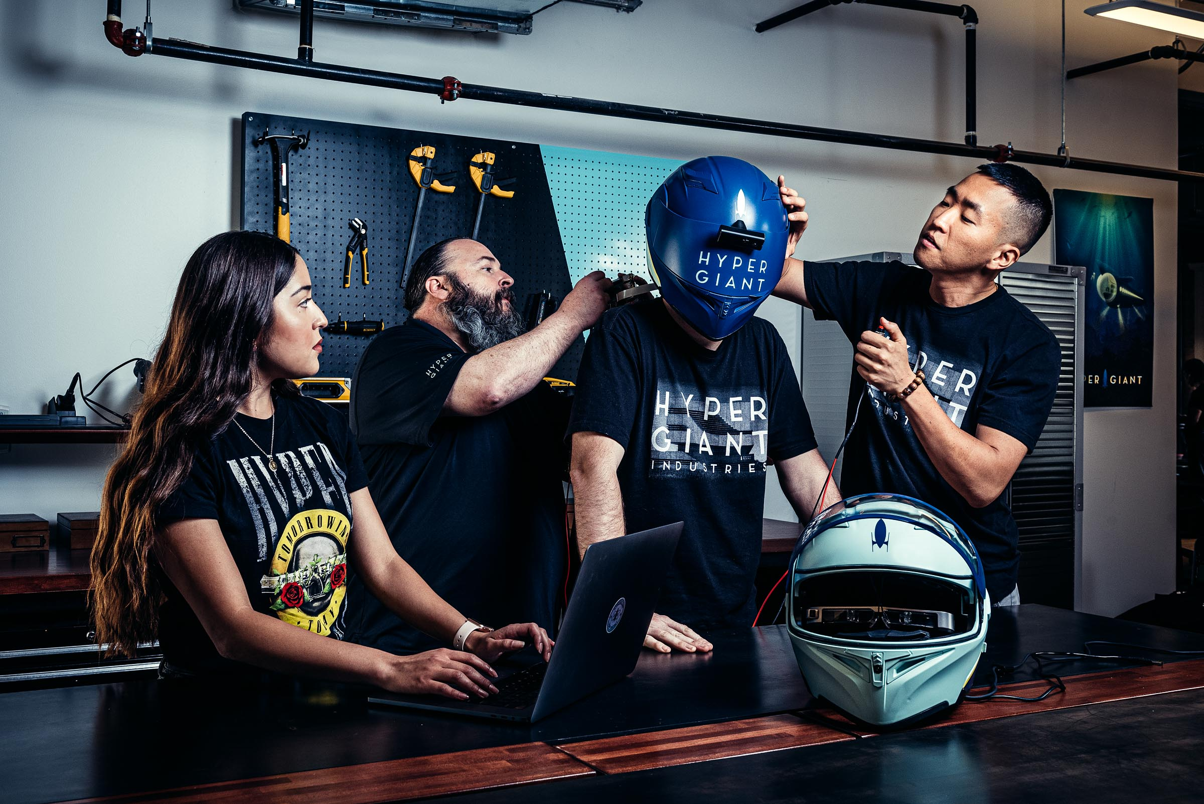 Corporate Lifestyle - Hypergiant AI Product Lab - Four colleagues work on a futuristic helmet