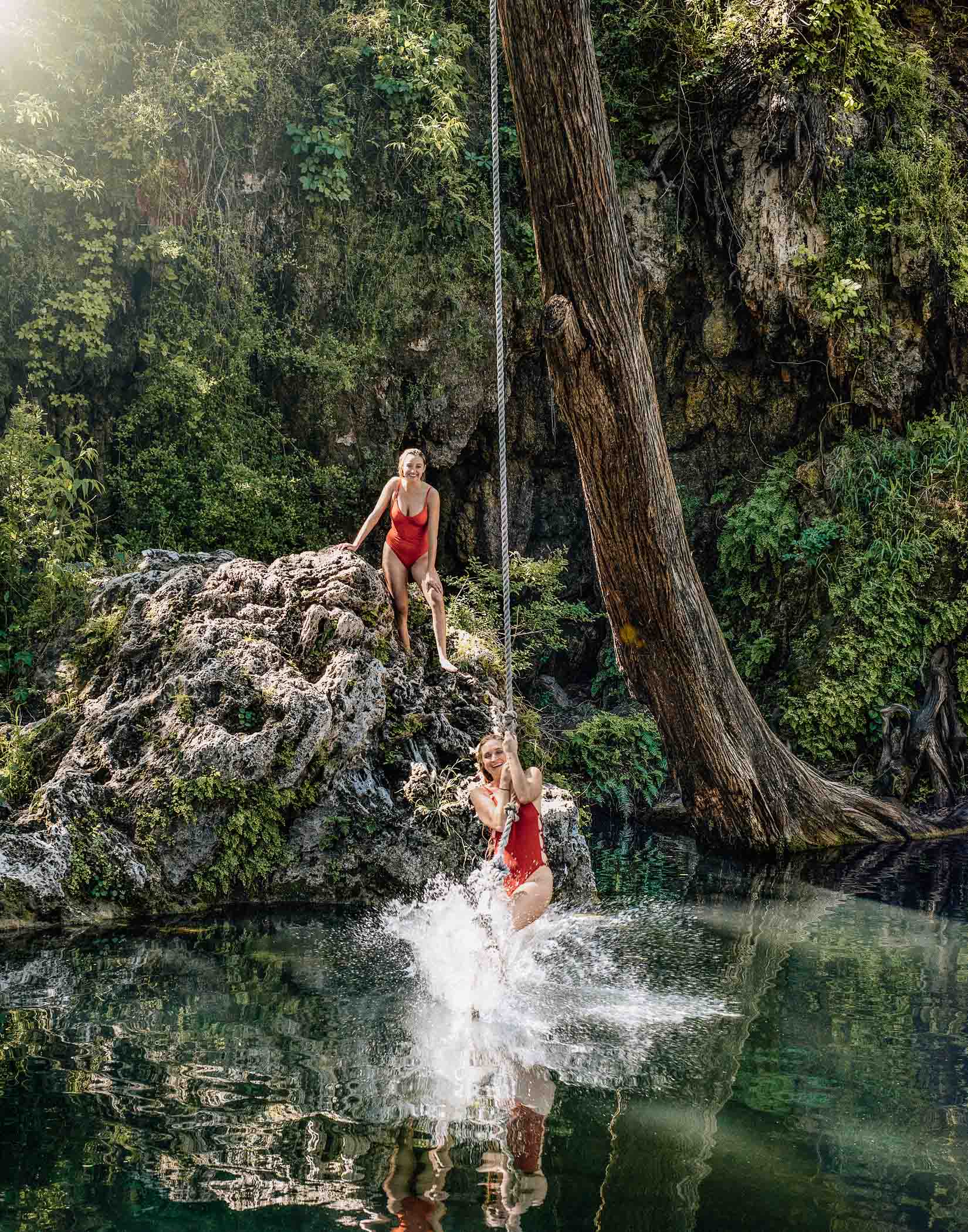 Young women enjoy a rope swing at Krause Springs water hole in TX