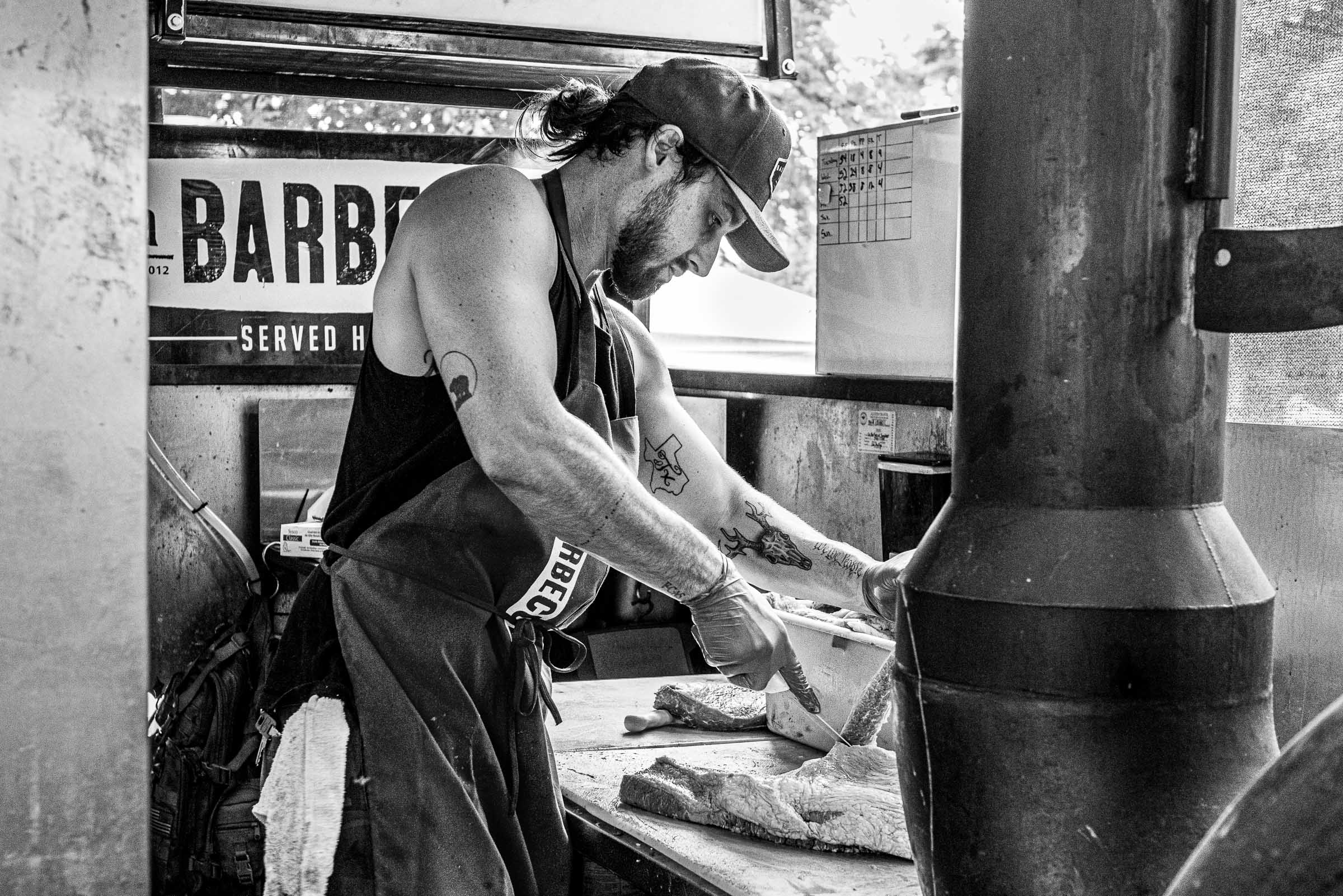 Black-and-white portrait of a butcher slicing meat at LaBarbecue-Texas-BBQ