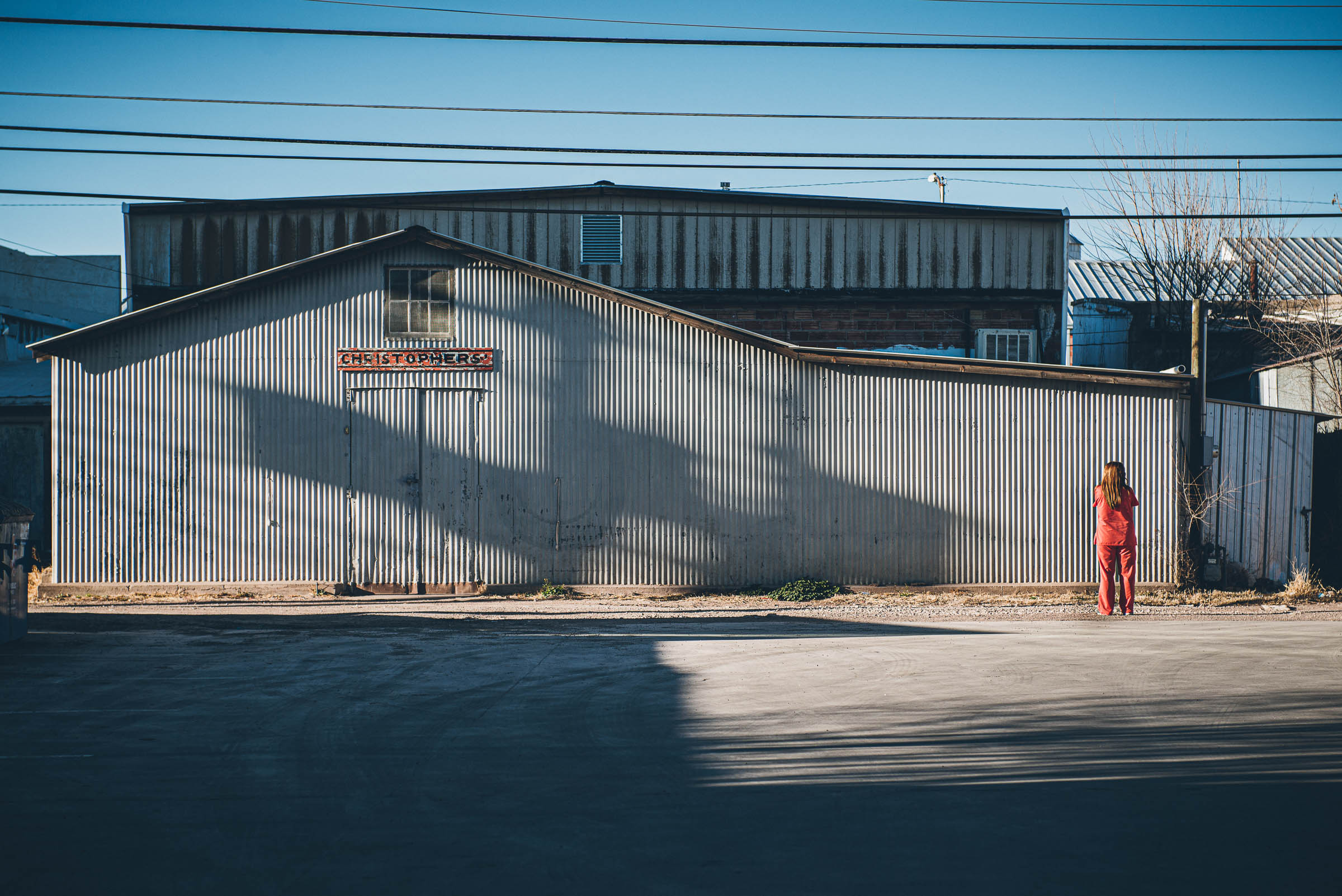 Lone woman in pink against industrial backdrop  -Marfa-Texas