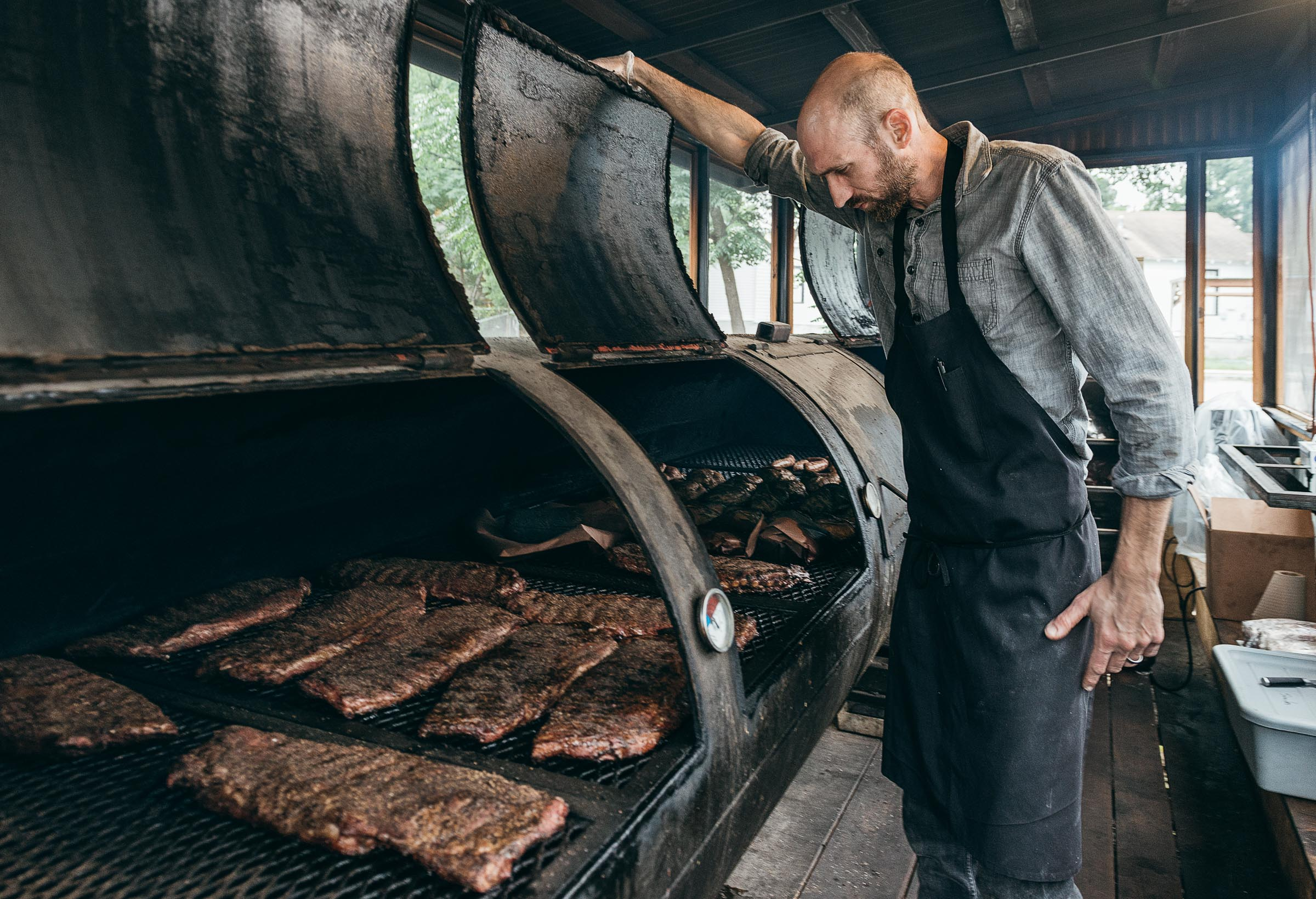 A tall, aproned man tending the meat smoker at Mickelthwaite-BBQ-Austin-TX