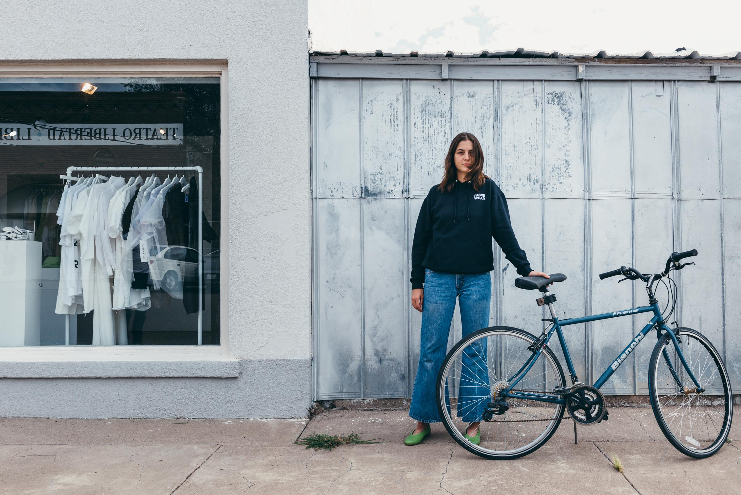 Street photography portrait - shop sales assistant with bicycle, Marfa TX