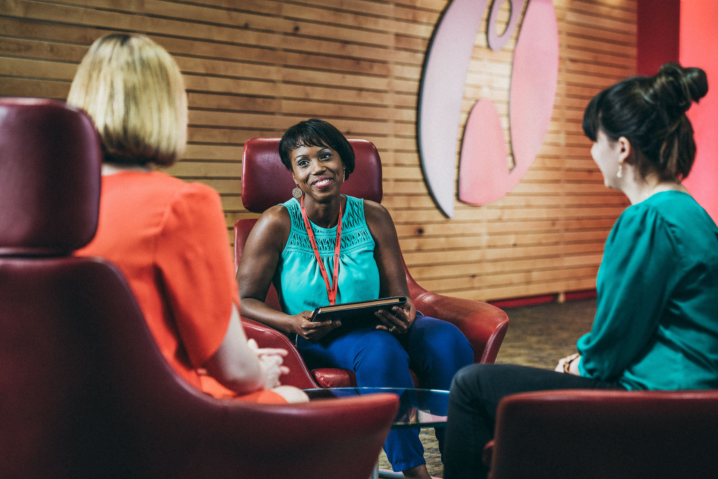 Business lifestyle photography -  three women talk in a colorful corporate environment.