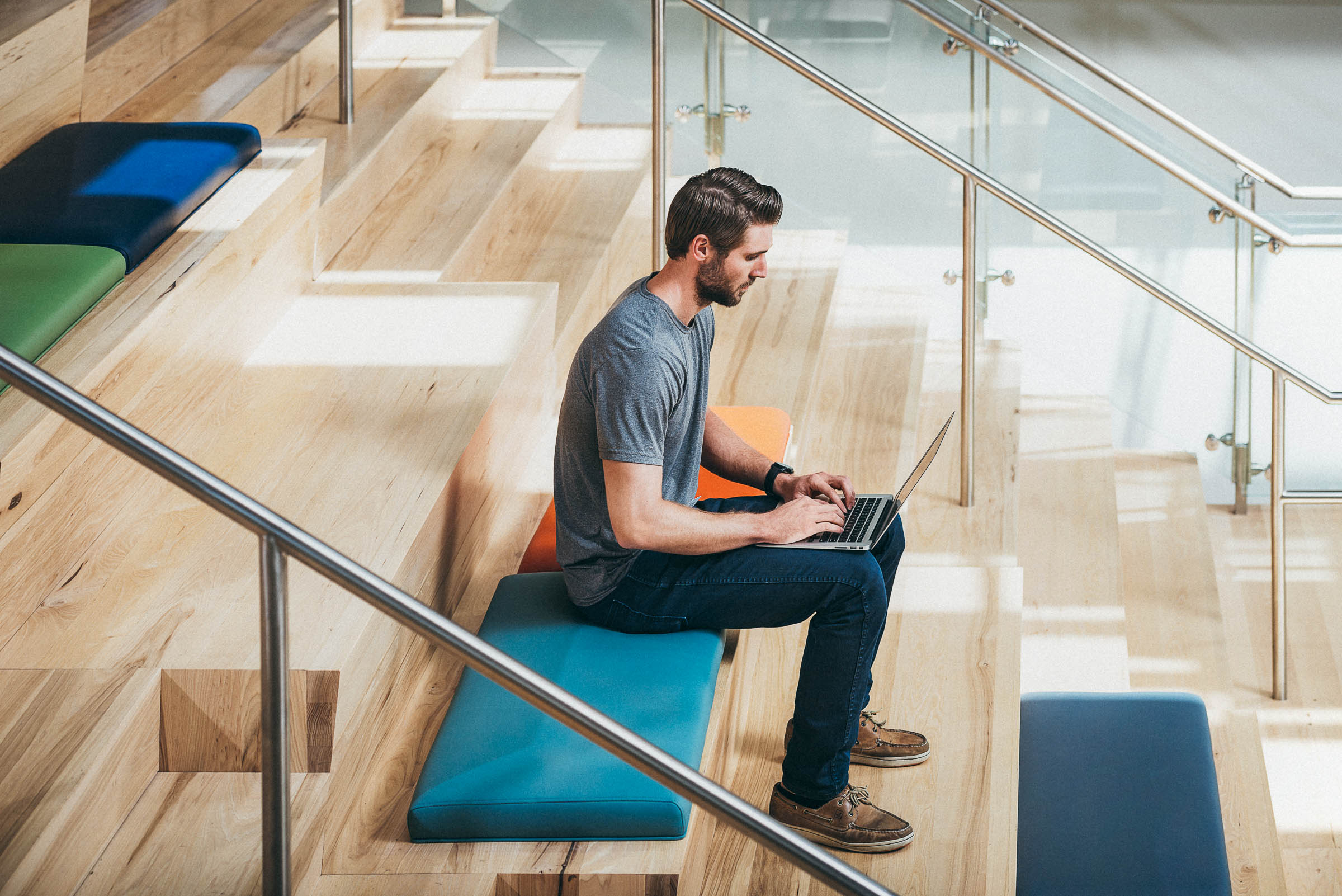 Tech lifestyle photography  - a stylish man works on his laptop, sitting on beautiful wood stairs.