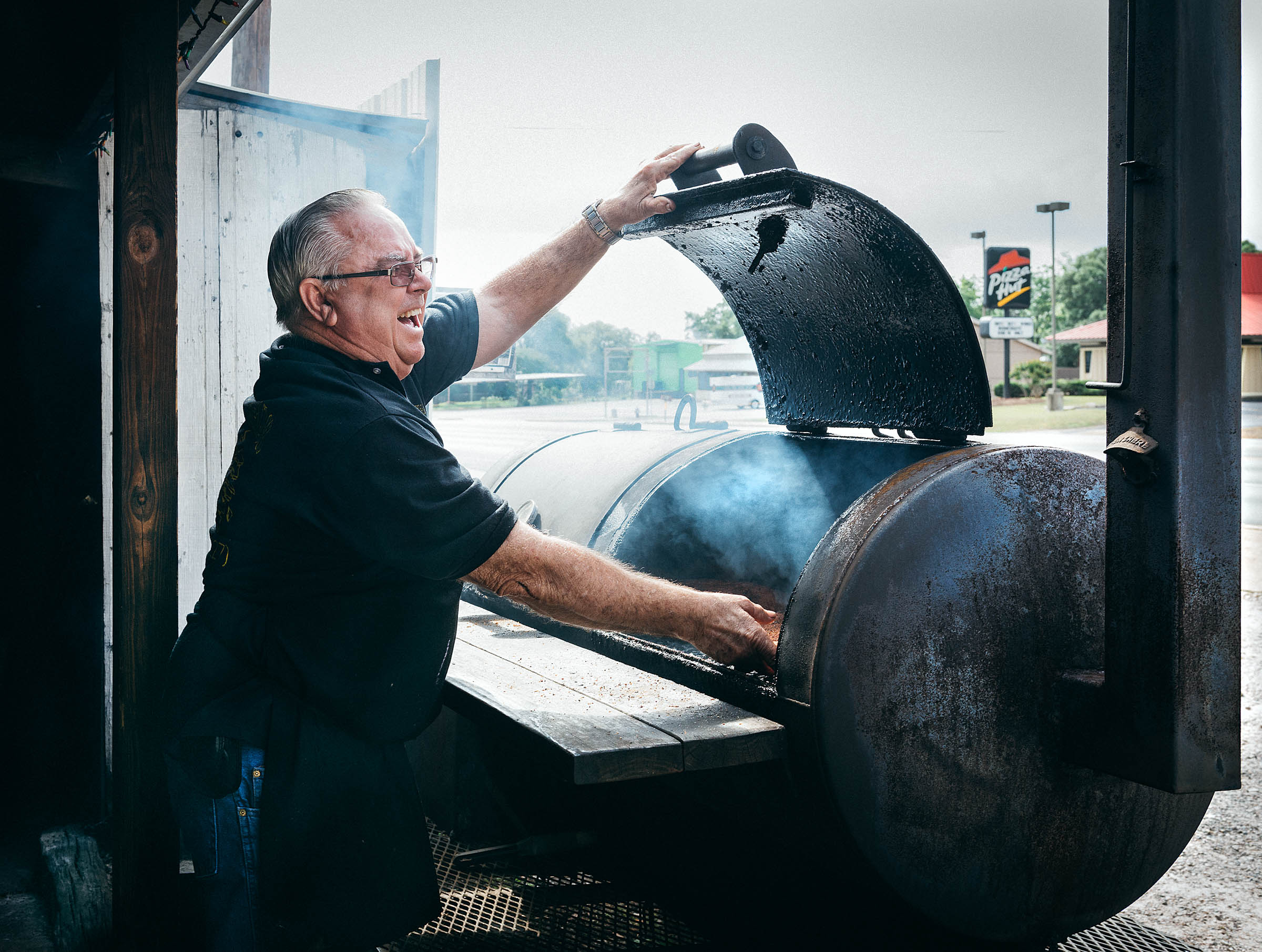 Pit-master Robert Payne of Paynes-BBQ in Burnet TX laughing as he opens his meat smoker.