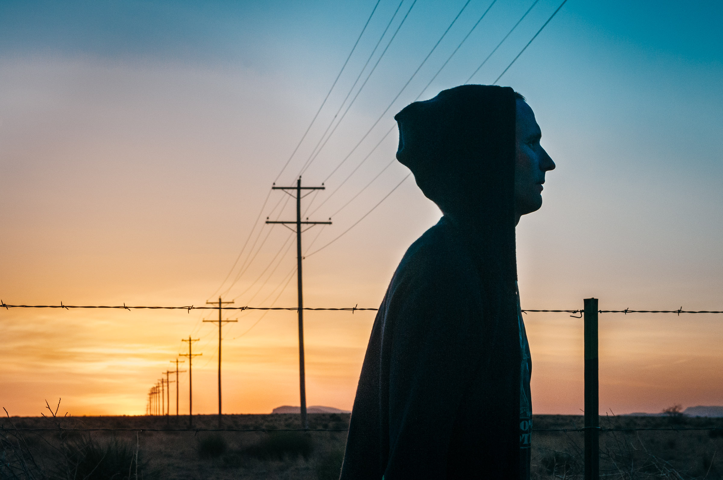 Hooded hipster in silhouette at sunset -West Texas.