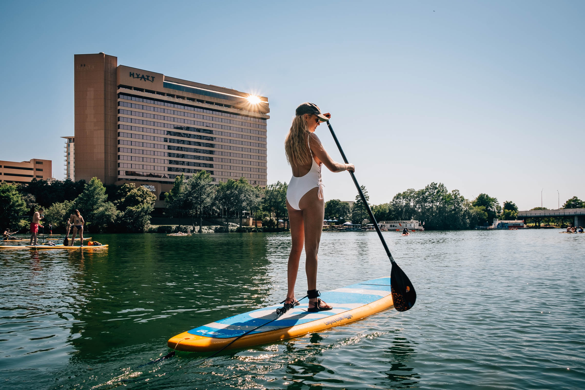 Summer travel - A paddle boarder in white bathing suit on Town Lake , Austin