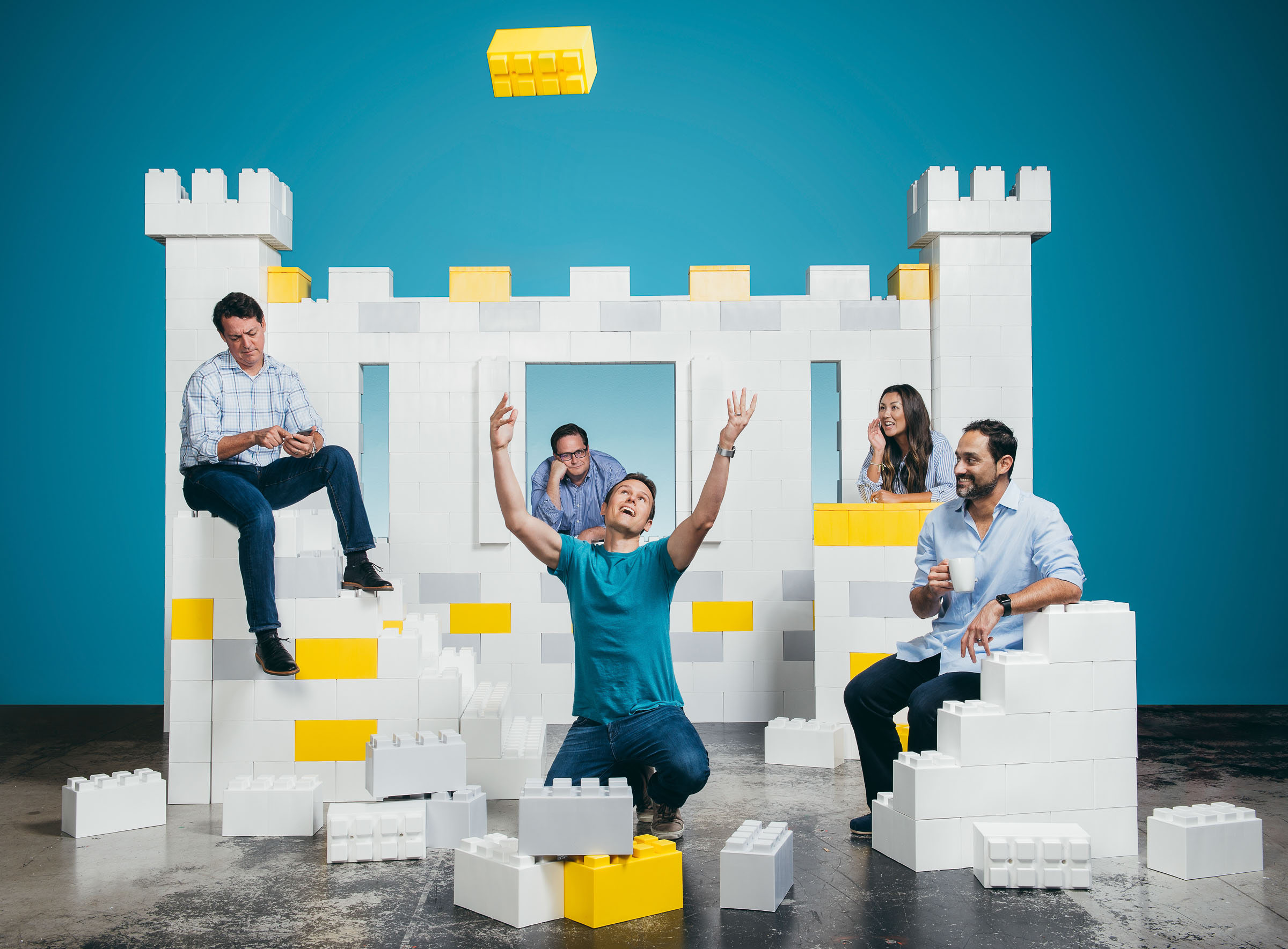 Corporate Lifestyle Photographer - Colleagues laughing at a giant Lego castle they have built.